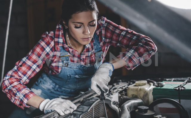 Female mechanic repairing car engine at workshop - FSIF02268