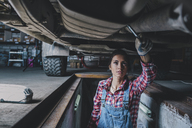 Female mechanic working underneath car at garage - FSIF02274