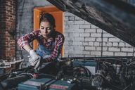 Female mechanic repairing car engine at garage - FSIF02277