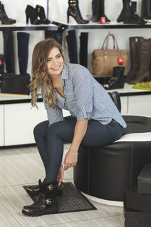 Happy woman looking away while trying on shoes at store - FSIF02289