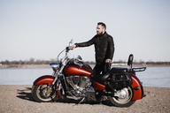 Full length portrait of biker standing by motorcycle and looking away at lakeshore - FSIF02292