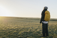 Rear view of female hiker standing on field against clear sky during sunrise - FSIF02298