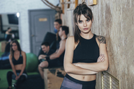 Portrait of confident female athlete standing arms crossed with friends in background at health club - FSIF02304