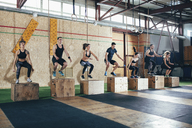 Full length of determined athletes doing box jumping at gym - FSIF02313