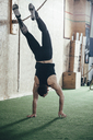 Rear view of sportsman doing handstand in gym - FSIF02316