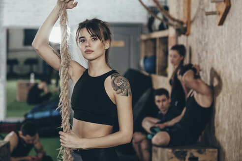 Portrait of confident female athlete holding rope while standing at gym with friends in background - FSIF02319
