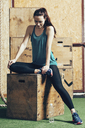 Full length of female athlete sitting on wooden box at gym - FSIF02322
