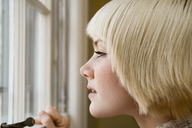 Young woman looking out a window - FSIF02340