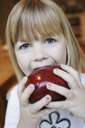 A young girl eating a red apple - FSIF02385