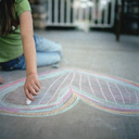 Young girl drawing a heart in chalk - FSIF02403