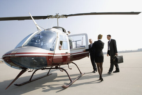 Woman assisting businessmen board a helicopter - FSIF02415