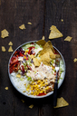 Taco salad bowl with rice, corn, chili con carne, kidney beans, iceberg lettuce, sour cream, nacho chips, tomatoes - SBDF03466