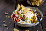 Taco salad bowl with rice, corn, chili con carne, kidney beans, iceberg lettuce, sour cream, nacho chips, tomatoes - SBDF03469