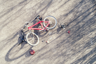 Bicycle, cycling helmet and repair tools on tarmac - MAEF12530