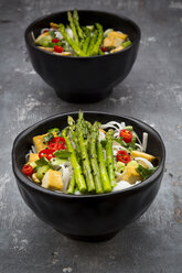 Bowl of vegan Pad Thai with mini green asparagus and tofu, chili, spring onion, peanut and coriander - LVF06725