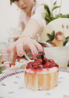 A woman reaching for a cake - FSIF02482