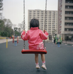Rear view of a young girl sitting on a swing - FSIF02488