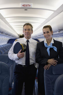 A pilot and a flight attendant standing in the cabin of a plane - FSIF02593