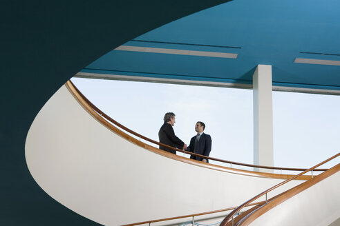 Two businessmen standing on a balcony and shaking hands - FSIF02605
