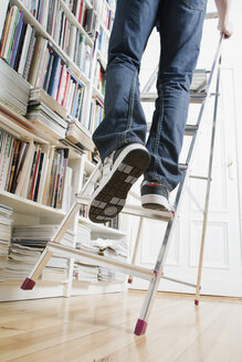 A man's legs climbing up a ladder that's about to tip over - FSIF02608