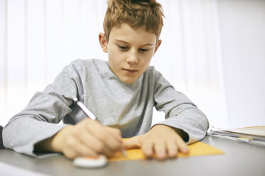 Schoolboy writing on desk in class - ZEDF01188