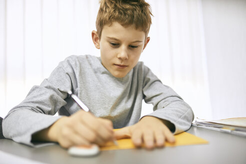 Schoolboy writing on desk in class - ZEDF01188