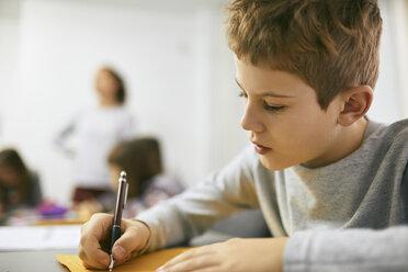 Schoolboy writing on desk in class - ZEDF01191