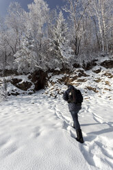 Russia, Amur Oblast, back view of man walking in snow-covered nature - VPIF00309