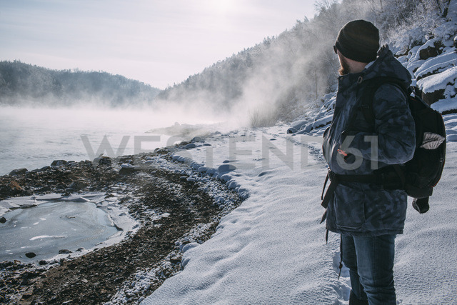 Russia, Amur Oblast, man standing in snow-covered landscape looking at  Bureya River - VPIF00312