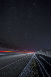 Russia, Amur Oblast, empty country road under starry sky in winter - VPIF00321