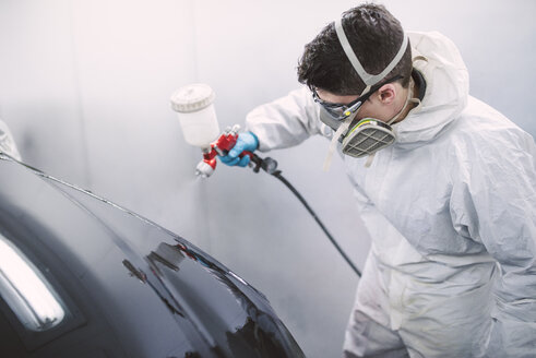 Auto painter painting a car inside a paint booth - RAEF01973