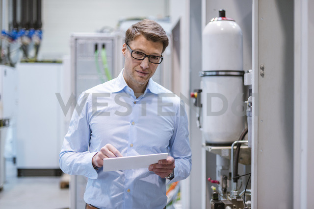 Portrait of businessman in factory holding tablet - DIGF03408
