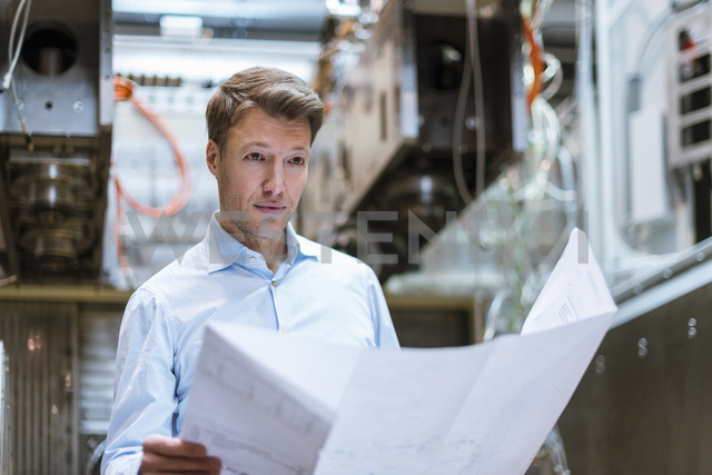 Businessman in factory holding plan - DIGF03411