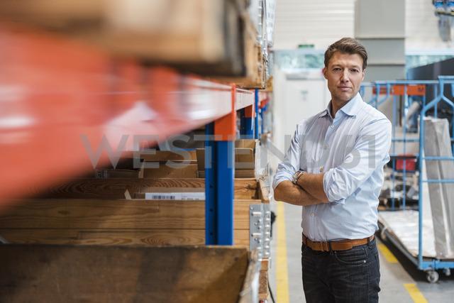 Portrait of confident businessman in factory storeroom - DIGF03417