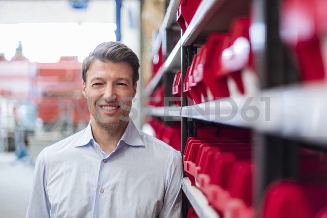 Portrait of smiling man at shelf in factory storeroom - DIGF03426