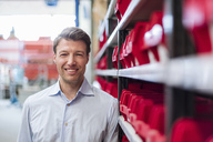 Portrait of smiling man at shelf in factory storeroom - DIGF03426