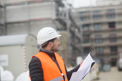 Man with plan wearing safety vest and hard hat at construction site - SGF02190