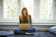 Redheaded woman sitting in front of window using laptop - FMKF04857