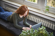 Redheaded woman lying on bench near heater using laptop - FMKF04860