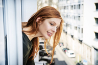 Portrait of smiling redheaded woman leaning out of window - FMKF04863