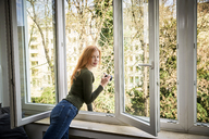 Portrait of smiling redheaded woman leaning out of window - FMKF04866