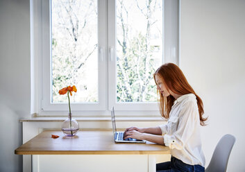 Redheaded woman sitting at table in front of window using laptop - FMKF04869