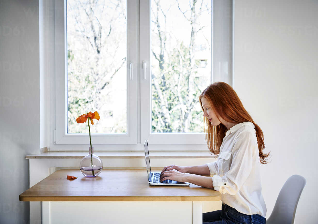 Redheaded woman sitting at table in front of window using laptop - FMKF04869 - Jo Kirchherr/Westend61