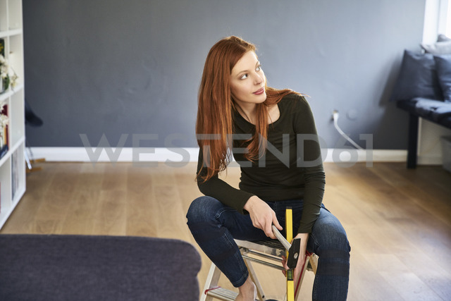 Redheaded woman with hammer and water level sitting on step ladder - FMKF04872