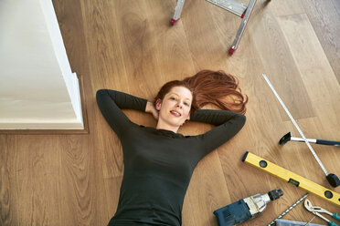 Redheaded woman lying beside tools on the floor - FMKF04875