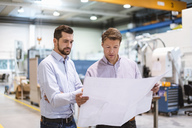 Two men in factory looking at plan - DIGF03428