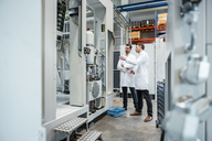 Two men wearing lab coats talking in factory - DIGF03443