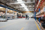 Two men wearing hard hats talking in factory shop floor - DIGF03446