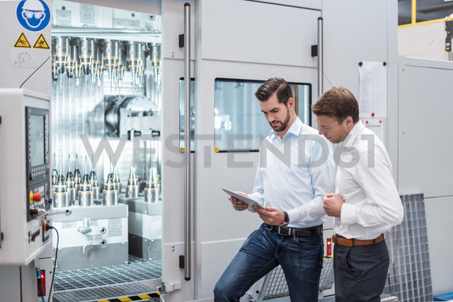 Two men standing at machine in factory looking at tablet - DIGF03452