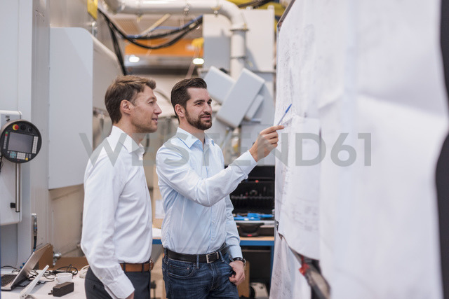 Two men in factory looking at plan - DIGF03455
